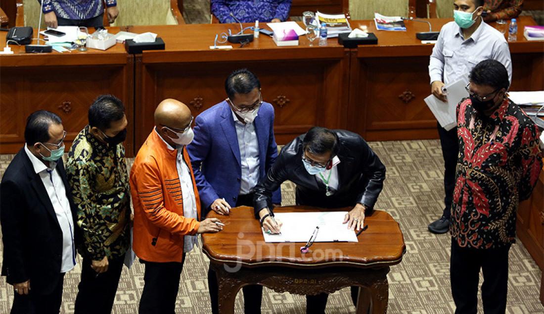 Menkumham Yasonna Laoly menandatangani naskah RUU tentang Mahkamah Konstitusi disaksikan Menpan RB Tjahjo Kumolo dan pimpinan Komisi III DPR pada rapat pengambilan keputusan tingkat I RUU tentang perubahan ketiga atas UU No 24 Tahun 2003 tentang MK dengan Komisi III DPR, Jakarta, Senin (31/8). Rapat membahas Penandatanganan Naskah RUU tentang MK dan pengambilan keputusan untuk melanjutkan pada Pembicaraan Tk, Il/Rapat Paripurna. Foto: Ricardo - JPNN.com