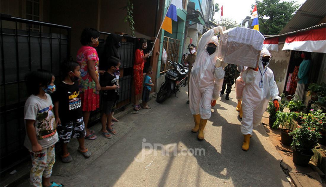 Petugas Kecamatan Cilandak membawa peti jenazah saat melakukan kampanye bahaya COVID-19 ke pemukiman warga, Jakarta, Selasa (1/9). Kampanye ini untuk mengimbau sekaligus mengajak masyarakat untuk selalu melakukan gerakan 3M yaitu Menggunakan Masker, Mencuci Tangan dan Menjaga Jarak. Foto: Ricardo - JPNN.com