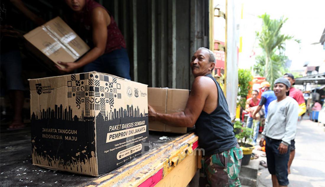 Warga menurunkan 562 paket bantuan sosial (bansos) dari Pemprov DKI Jakarta di Posko RW 13, Kelurahan Pademangan Barat, Jakarta Utara, Rabu (2/9). Paket bantuan tersebut berisi beras 5 kilogram, 4 kaleng sarden, 1 kaleng biskuit, minyak goreng, kecap, 1 kilogram tepung terigu, bihun dan sabun mandi. Foto: Ricardo - JPNN.com