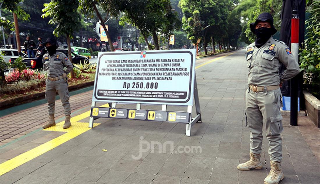 Petugas Satpol PP Kota Bogoe menghentikan pengendara sepeda di jalur pedestrian Kebun Raya Bogor, Jawa Barat, Sabtu (19/9). Pemkot Bogor menutup aktivitas warga di jalur pedestrian Kebon Raya Bogor dan Istana Bogor pada masa Pembatasan Sosial Berskala Mikro dan Komunitas (PSBMK) untuk mencegah penularan Covid-19. Foto: Ricardo - JPNN.com