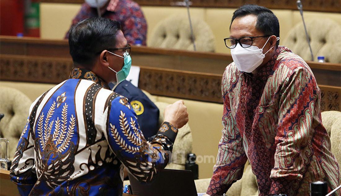 Anggota Komisi II DPR Nasir Djamil berbincang dengan Mendagri Tito Karnavian di sela rapat kerja dengan Mendagri, DKPP, KPU dan Bawaslu, Jakarta, Senin (21/9). Rapat ini membahas laporan tentang Rumusan dan Langkah-Langkah Penegakan Disiplin dan Sanksi Hukum terhadap Pelanggaran Protokol Kesehatan Covid-19, memastikan antisipasi potensi terjadinya pelanggaran protokol kesehatan Covid-19 pada tahapan penetapan paslon dan masa kampanye, serta evaluasi secara menyeluruh. Foto: Ricardo - JPNN.com