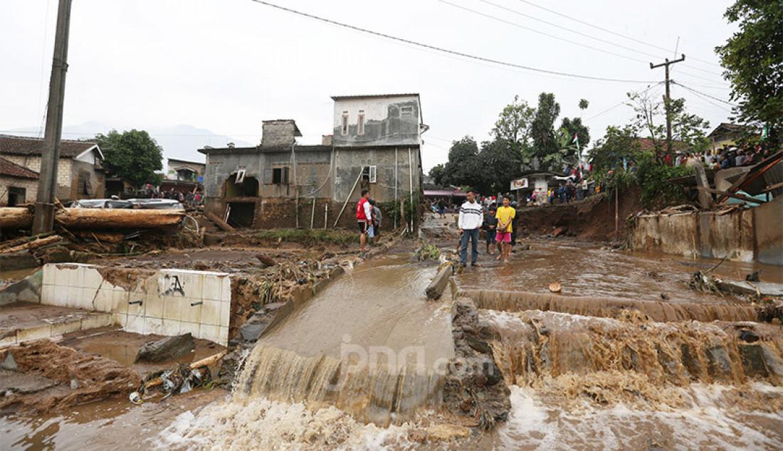 Warga menyaksikan sisa-sisa banjir di Kampung Cibuntu, Desa Pasawahan, Kecamatan Cicurug, Sukabumi, Selasa (22/9). Hujan disertai angin lebat mengakibatkan banjir membuat puluhan bangunan rusak berat, 12 bangunan rumah hanyut dan dua korban hilang masih dicari. Foto: Ricardo - JPNN.com