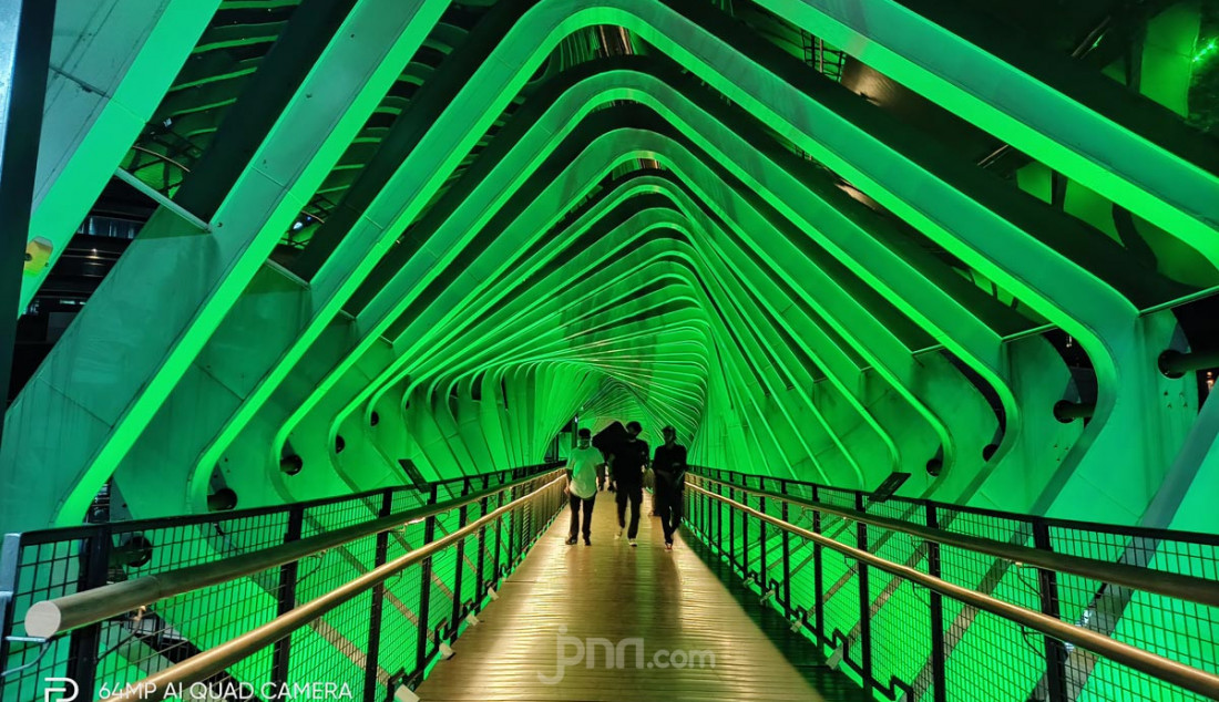 Pejalan kaki melintas di Jembatan Penyeberangan Orang (JPO) Gelora Bung Karno. Aktivitas warga Jakarta tampak sepi sejak diberlakukannya kembali PSBB, Jakarta, Sabtu (19/9). Foto diambil menggunakan kamera Realme 7 64MP sensor Sony IMX682 dengan memanfaatkan fitur Nightscape dan filter Flamingo sehingga gambar lebih terasa dramatis. Foto: Rasyid Ridha - JPNN.com
