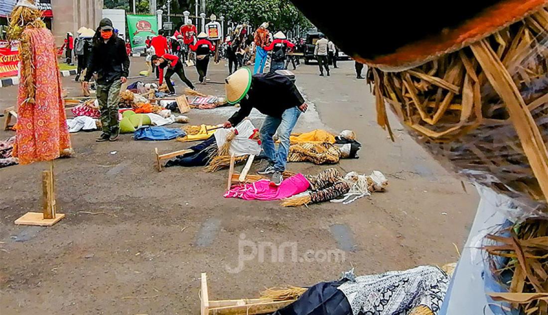 Sejumlah elemen dari aktivis hingga mahasiswa dari Komite Nasional Pembaruan Agraria (KNPA) dan Gerakan Mahasiswa Nasional Indonesia (GMNI) melakukan aksi demonstrasi dalam rangka Hari Tani Nasional di depan gedung DPR RI, Senayan, Jakarta, Kamis (24/9). Aksi itu menampilkan orang-orangan sawah yang dipasang berjajar di depan gerbang masuk Kompleks Parlemen dengan spanduk bertuliskan jangan ada klaster tani saat pandemi virus Corona (COVID-19). Foto: Ricardo - JPNN.com