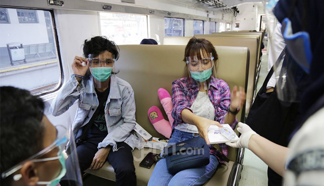 Penumpang kereta api di Stasiun Pasar Senen, Jakarta Pusat menerima masker dan hand sanitizer dari PT KAI, Senin (28/9). PT KAI membagi-bagikan masker dan hand sanitizer secara gratis kepada para penumpang kereta dalam rangka peringatan ulang tahunnya yang ke-75. Foto: Ricardo - JPNN.com
