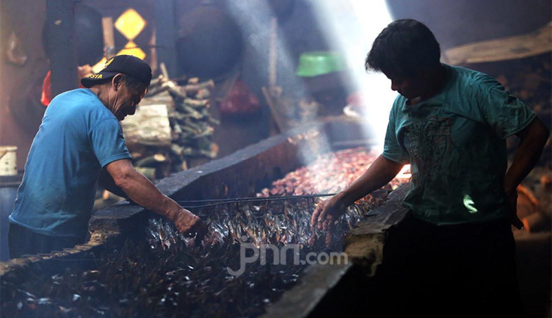 Pekerja menyusun ikan lele yang diasapi di Kelurahan Pengasinan, Kecamatan Gunung Sindur, Kabupaten Bogor, Jawa Barat, Rabu (30/9). Ikan lele diasapi selama dua hari sebelum dipasarkan di wilayah Jabodetabek, bahkan diekspor ke Nigeria. Foto: Ricardo - JPNN.com