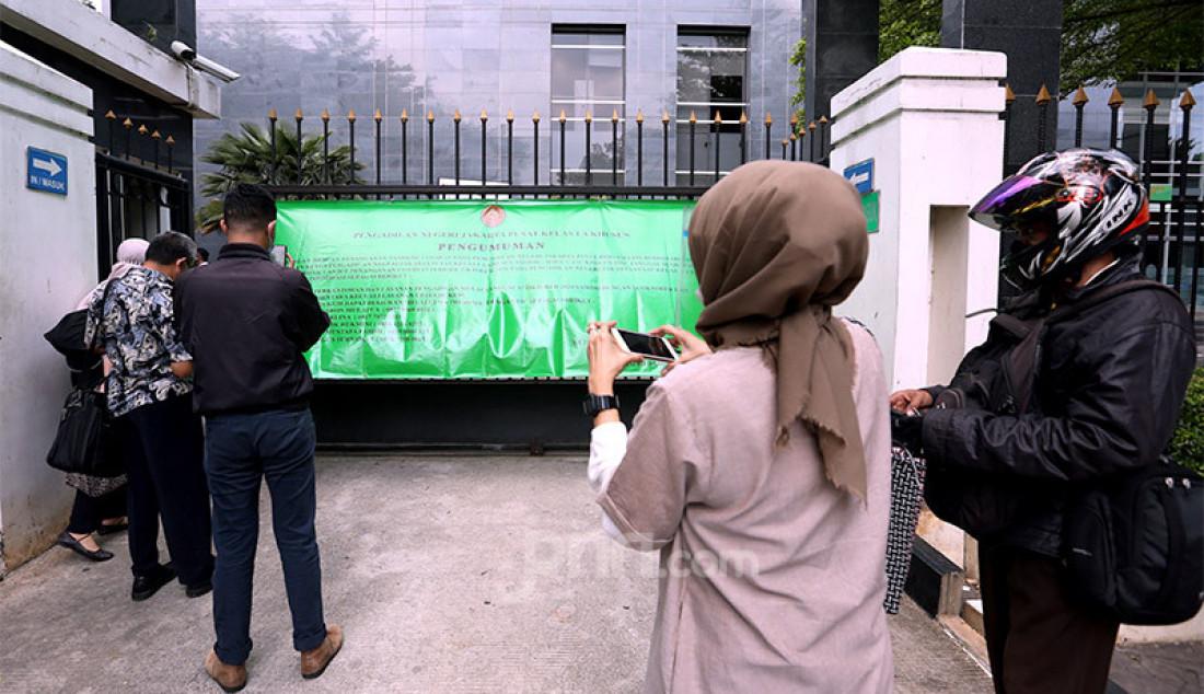 Sejumlah penggunjung Pengadilan Negeri Jakarta Pusat (PN Jakpus) di Jakarta, Rabu (7/10) membaca pengumuman di pagar terkait penutupan sementara pada 7-9 Oktober 2020. PN Jakpus melakukan lockdown selama 3 hari setelah ada pegawainya yang terjangkiti Covid-19. Foto: Ricardo - JPNN.com