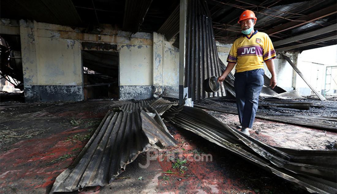 Seorang pekerja melihat kondisi gedung bioskop Grand Theater di Pasar Senen, Jakarta Pusat yang hangus terbakar saat aksi unjuk rasa menolak Omnibus Law Cipta Kerja, Jumat (9/10) berakhir rusuh. Foto: Ricardo - JPNN.com