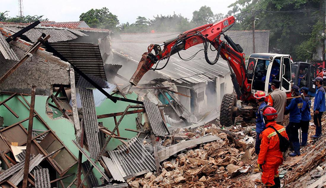 Petugas Suku Dinas Sumber Daya Air Kota Jakarta Selatan mengoperasikan alat berat untuk membersihkan puing rumah di Jalan Damai, Ciganjur,Senin (12/10). Sejumlah rumah di kawasan tersebut rusak akibat tanah longsor saat hujan deras beberapa waktu lalu. Foto: Ricardo - JPNN.com