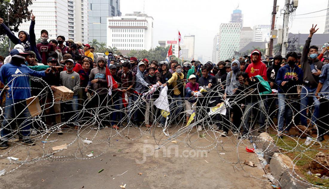 Pedemo pada aksi unjuk rasa menolak Omnibus Law Cipta Kerja merusak pagar kawat yang dipasang petugas di kawasan Kebun Sirih, Jakarta Pusat, Selasa (13/10). Foto: Ricardo - JPNN.com