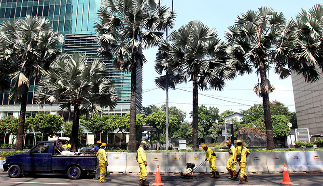Petugas memperbaikan aspal di Jalan Thamrin, Jakarta Pusat, Rabu (14/1). Aspal di ruas jalan utama ibu kota itu rusak pascademo menolak Omnibus Law Cipta Kerja pada Kamis (8/10) yang berakhir rusuh. Foto: Ricardo - JPNN.com