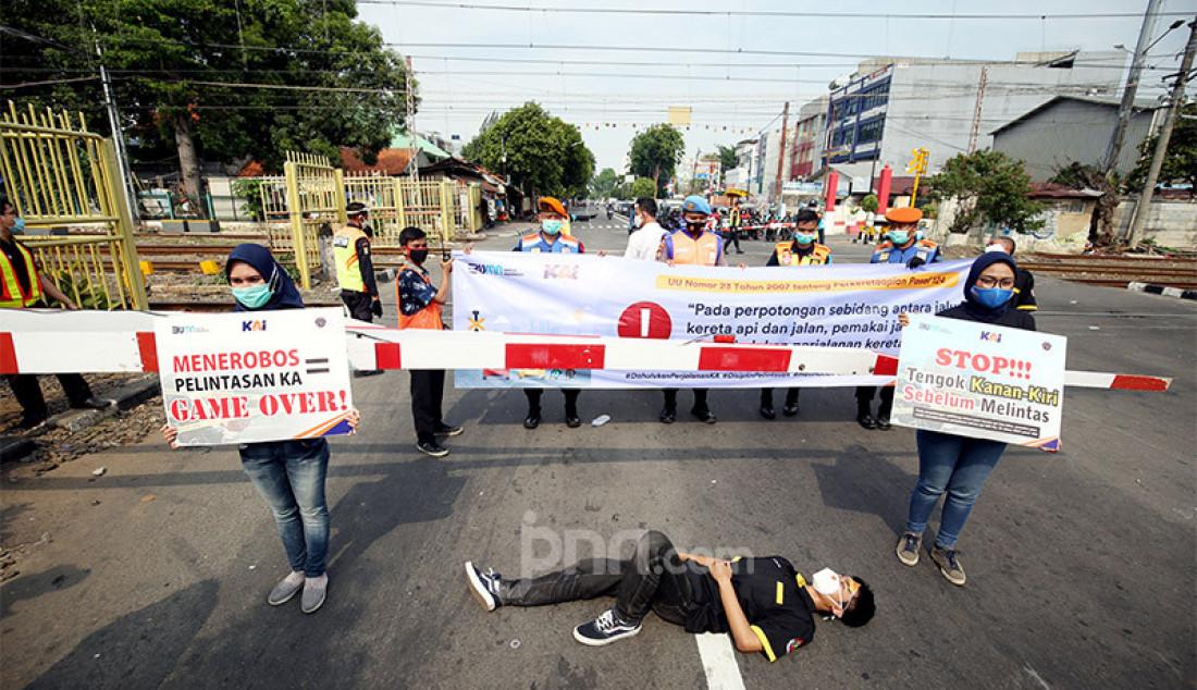 Volunter dari Pecinta Kereta Api bersama PT KAI melakukan sosialisasi pelintasan sebidang di Jalan Garuda, Kemayoran, Jakarta Pusat, Rabu (14/10). Foto: Ricardo - JPNN.com