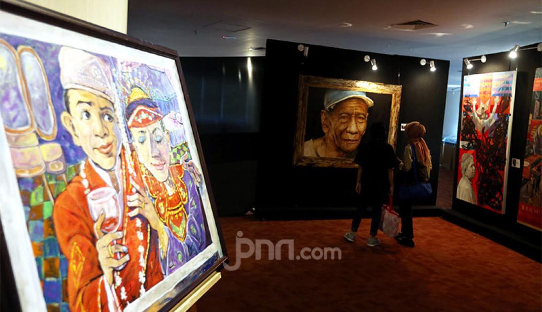 Pengunjung mengamati karya seni yang ditampilkan dalam pameran seni rupa bertajuk