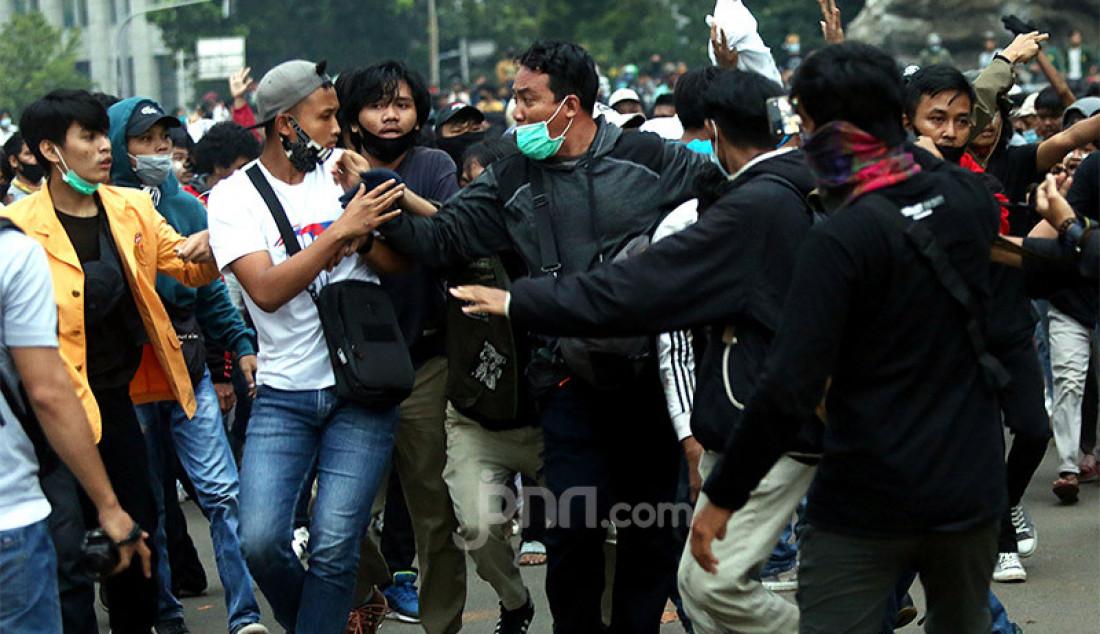 Sejumlah demonstran berusaha menghajar copet yang diamankan petugas saat aksi unjuk rasa menolak Omnibus Law Cipta Kerja di kawasan Patung Kuda, Jalan Medan Merdeka Barat, Jakarta, Selasa (20/10). Foto: Ricardo - JPNN.com