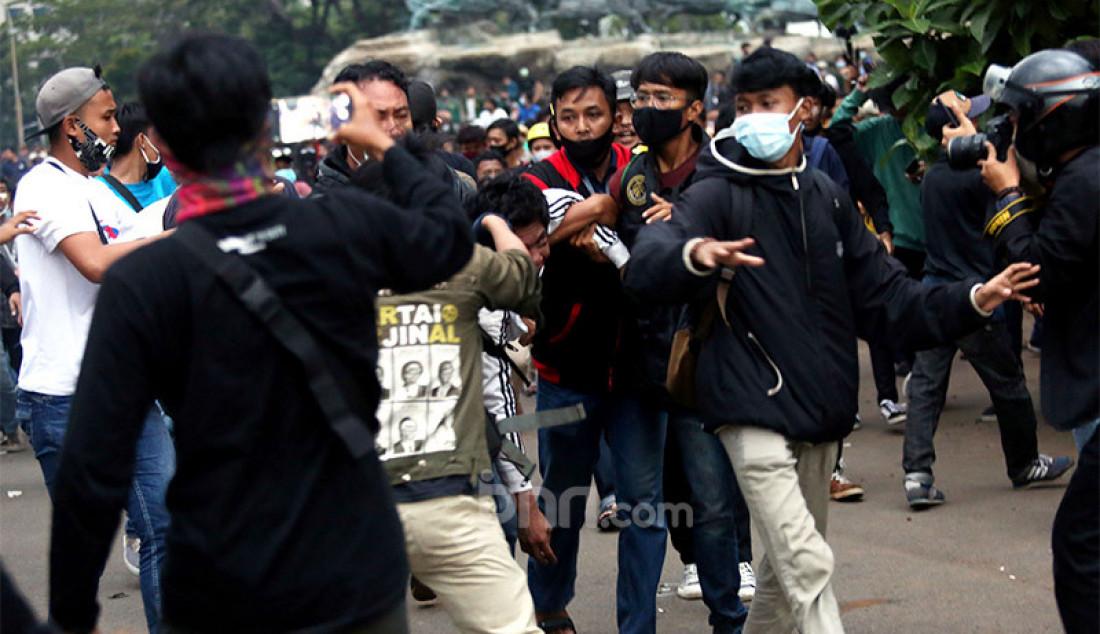 Sejumlah demonstran berusaha menghakimi copet yang diamankan petugas saat aksi unjuk rasa menolak UU Cipta Kerja di sekitar kawasan Patung Kuda, Jalan Medan Merdeka Barat, Jakarta, Selasa (20/10). Foto: Ricardo - JPNN.com