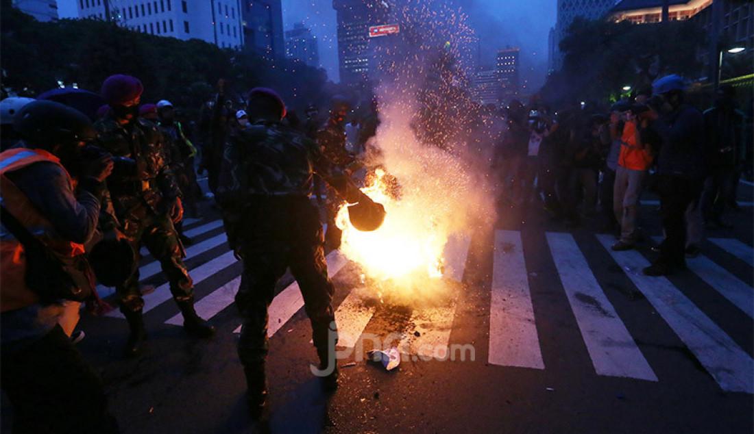 Anggota Korps Marinir memadamkan api buatan pengunjuk rasa yang menolak Omnibus Law Cipta Kerja di kawasan Patung Kuda, Jalan Medan Merdeka Barat, Jakarta, Selasa (20/10). Foto: Ricardo - JPNN.com