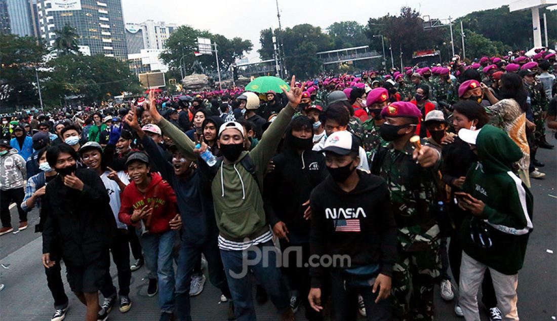 Korps Marinir mengawal massa yang baru saja berunjuk rasa menolak Omnibus Law Cipta Kerja di kawasan Patung Kuda, Jalan Medan Merdeka Barat, Jakarta, Selasa (20/10). Foto: Ricardo - JPNN.com