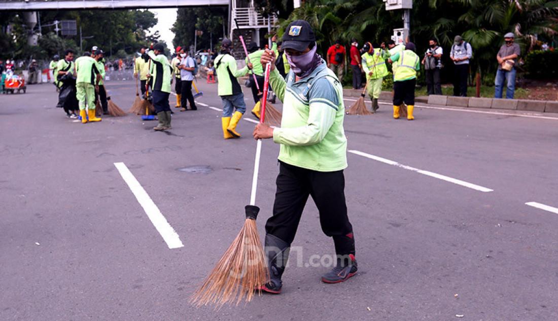 Petugas kebersihan membersihkan sampah sisa aksi demo menolak Omnibus Law Cipta Kerja di kawasan Patung Kuda, Jakarta Pusat, Kamis (22/10). Foto: Ricardo - JPNN.com