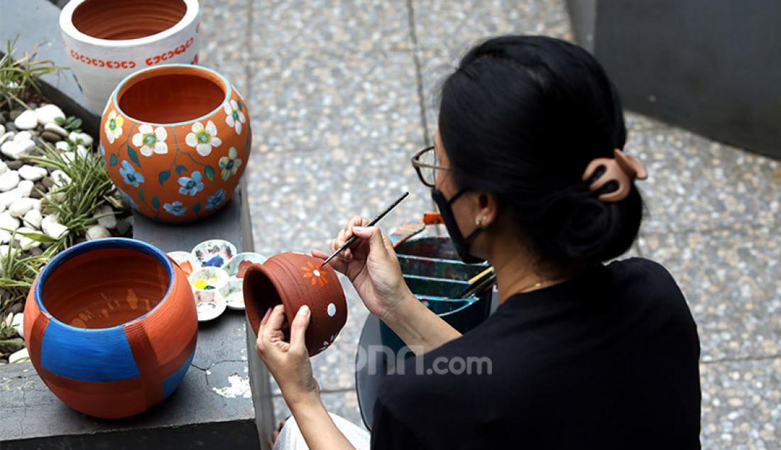 Pelukis Dara Sinta (50 tahun) melukis pot tanah liat di Rumah Dara Painting Gallery, Perumahan Taman Yasmin, Bogor, Sabtu (24/10). Seniman lukis tersebut tetap berkarya di tengah pandemi COVID-19 dengan melukis melalui berbagai media seperti masker kain, pot tanah liat dan botol minum bekas. Foto: Ricardo - JPNN.com