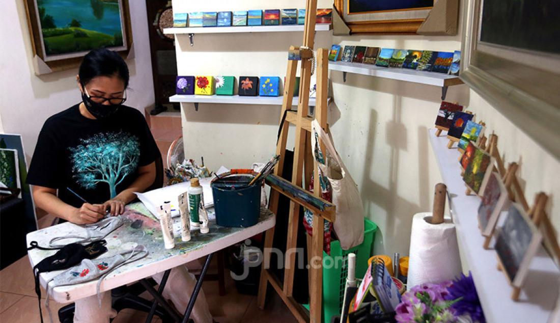 Pelukis Dara Sinta (50 tahun) di Rumah Dara Painting Gallery, Perumahan Taman Yasmin, Bogor, Sabtu (24/10) saat mengerjakan pesanan masker dengan motif lukisan. Seniman lukis tersebut tetap berkarya di tengah pandemi COVID-19 dengan melukis melalui berbagai media seperti masker kain, pot tanah liat dan botol minum bekas. Foto: Ricardo - JPNN.com