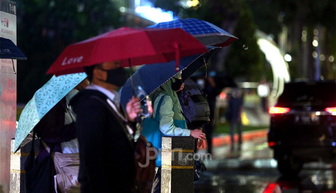 Warga menggunakan payung saat hujan turun di kawasan Jalan Jendral Sudirman, Jakarta Pusat, Senin (26/10). Badan Penanggulangan Bencana Daerah (BPBD) DKI Jakarta telah mengeluarkan peringatan dini tentang curah hujan tinggi disertai angin kencang selama tiga hari. Foto: Ricardo - JPNN.com