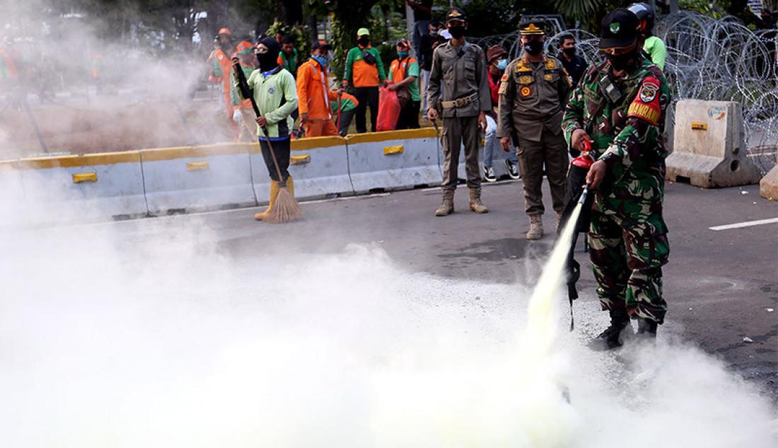 Anggota TNI memadamkan ban yang dibakar oleh massa saat aksi unjuk rasa menolak Undang-Undang Cipta Kerja di kawasan Patung Kuda, Jakarta, Rabu (28/10). Foto: Ricardo - JPNN.com