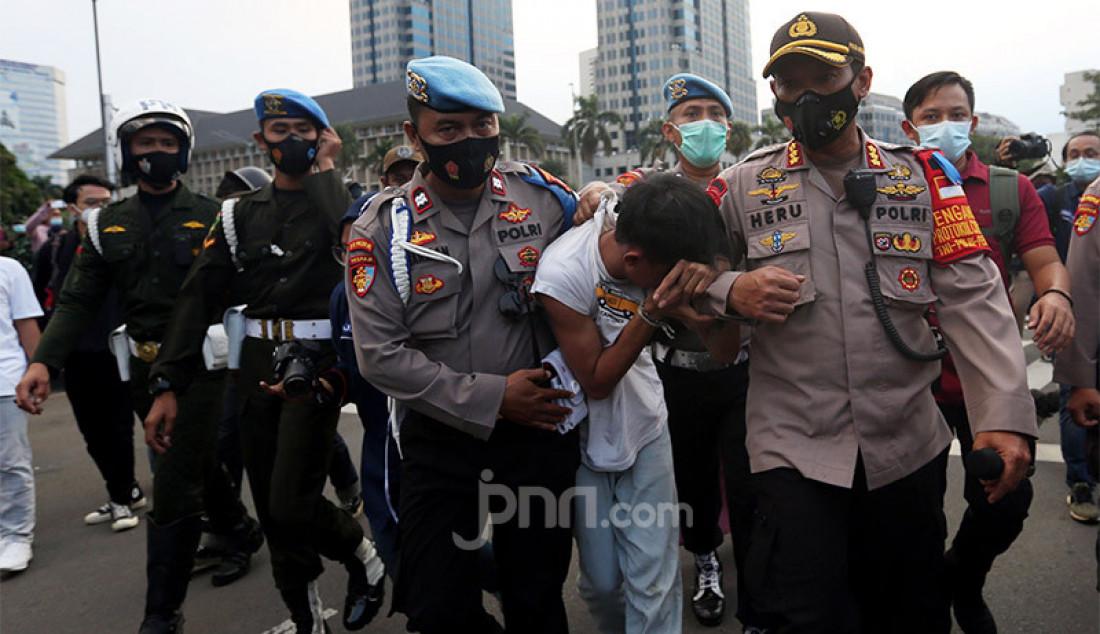 Petugas kepolisian mengamankan copet yang tertangkap tangan saat bubaran massa demo menolak UU Cipta Kerja di Kawasan Patung Kuda, Jakarta, Rabu (28/10). Foto: Ricardo - JPNN.com