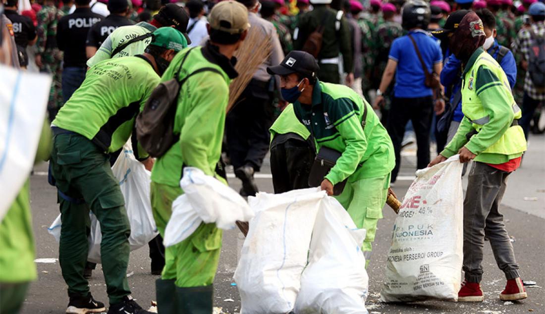 Petugas kebersihan memberikan sampah-sampah usai demo UU Cipta Kerja di Kawasan Patung Kuda, Jakarta, Rabu (28/10). Foto: Ricardo - JPNN.com