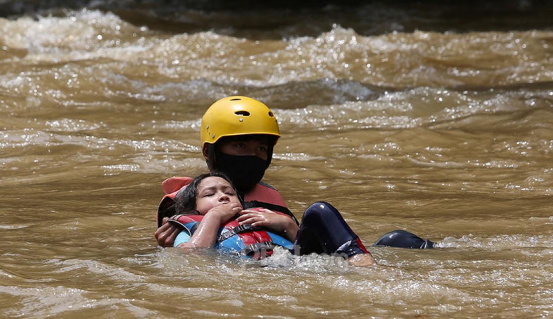Instruktur Hiking Bocah mendampingi seorang anak yang terjatuh dari perahu karet saat mengikuti rafting di kawasan Bendung Katulampa, Bogor, Kamis (29/10). Kegiatan yang diadakan Hiking Bocah pada setiap akhir pekan atau libur panjang itu dalam rangka mengenalkan lingkungan alam kepada anak-anak. Foto: Ricardo - JPNN.com