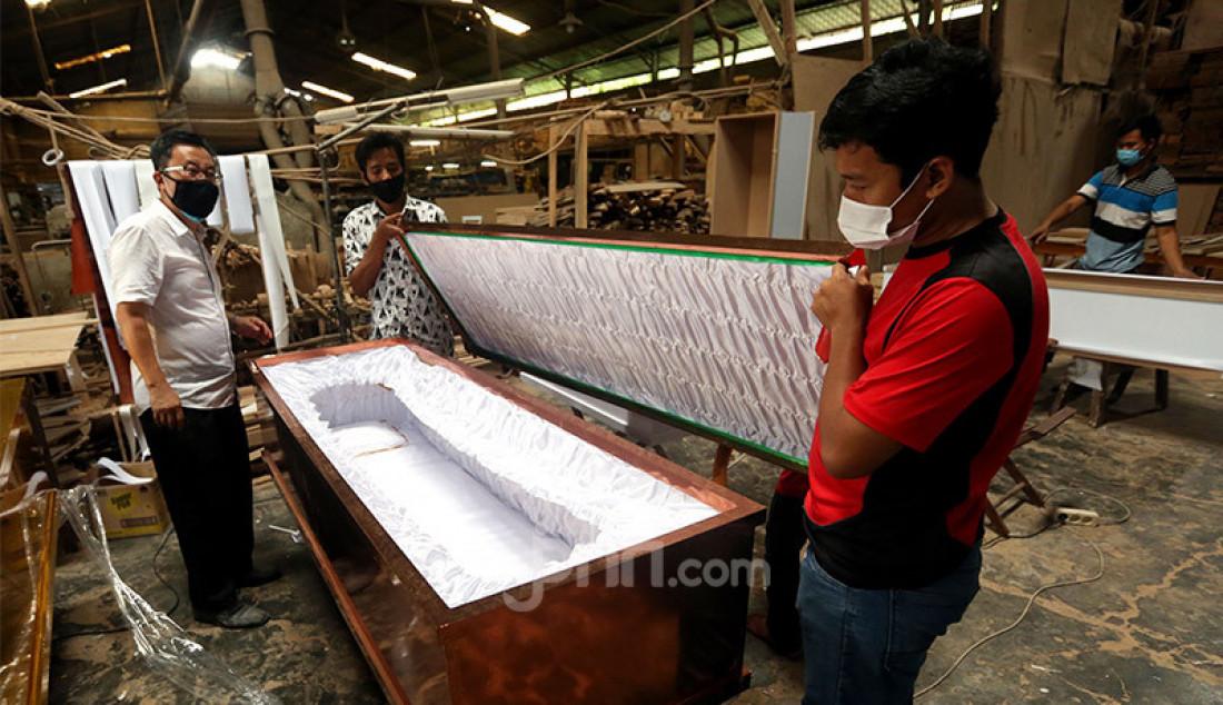 Sejumlah pekerja di pabrik Hakari Furniture, kawasan Daan Mogot, Jakarta Barat, Jumat (30/10) menyelesaikan pesanan peti mati khusus jenazah Covid-19. Hakari Furniture mampu membuat 100 peti mati khusus jenazah korban Covid-19 per hari. Foto: Ricardo - JPNN.com