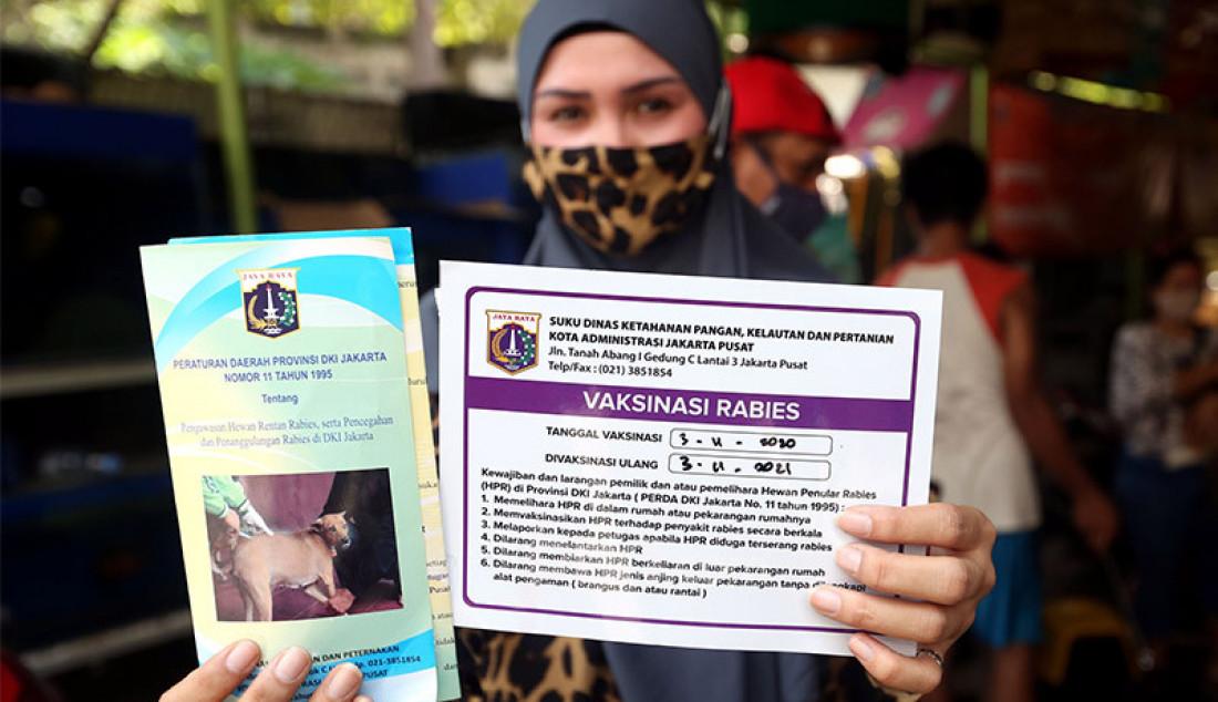 Seorang warga menunjukkan tanda bukti usai memvaksinasi hewan peliharaan miliknya, Jakarta, Selasa (3/11). Kegiatan vaksinasi itu dilakukan oleh Suku Dinas ketahanan Pangan, Kelautan dan Perikanan (KPKP) Jakarta Pusat untuk mencegah penularan Covid-19. Foto: Ricardo - JPNN.com