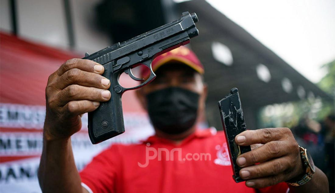 Seorang petugas menunjukkan senjata api jenis pistol yang akan dimusnahkan di halaman Kejaksaan Negeri, Jakarta Utara, Rabu (11/11). Pistol tersebut merupakan barang bukti perkara yang telah diputus pengadilan dan berkekuatan hukum tetap (inkrah). Foto: Ricardo - JPNN.com
