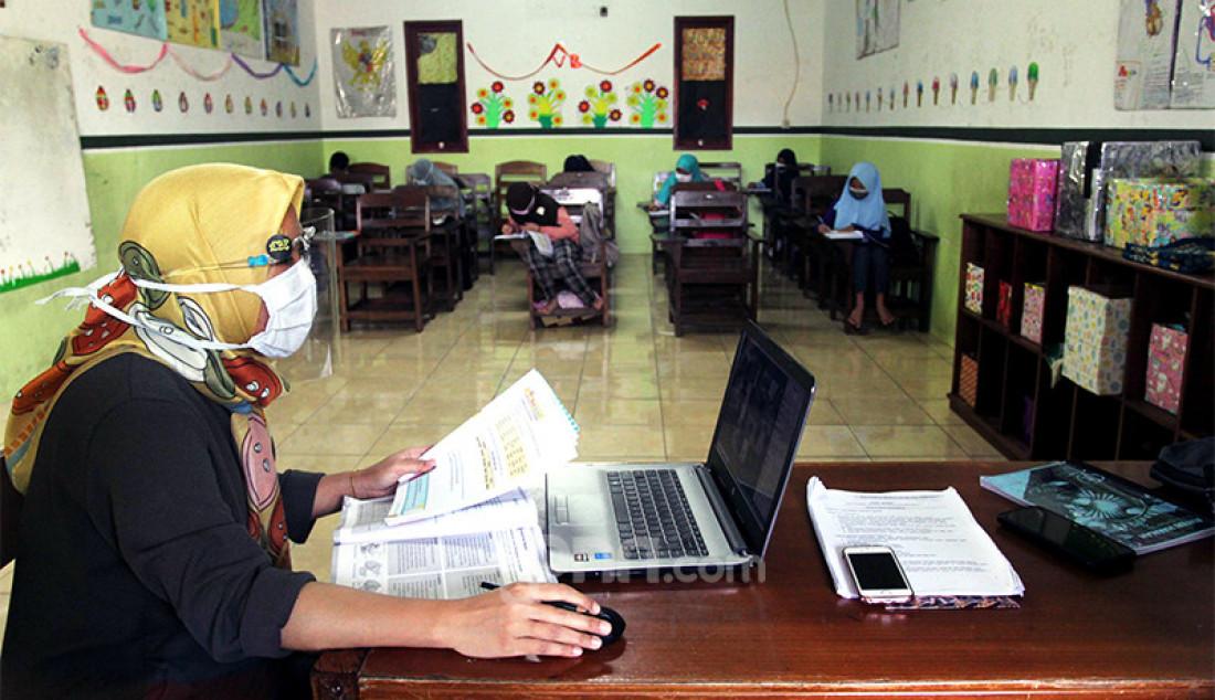 Guru di Sekolah Dasar Islam Terpadu (SDIT) Nurul Amal, Pondok Cabe, Tangerang Selatan, Banten, Senin (16/11) sedang mengajar secara daring sekaligus melakukan pembelajaran tatap muka dengan murid. Proses pembelajaran secara tatap muka itu dilakukan dengan pembatasan jumlah murid dalam satu kelas dan menerapkan protokol kesehatan. Foto: Ricardo - JPNN.com