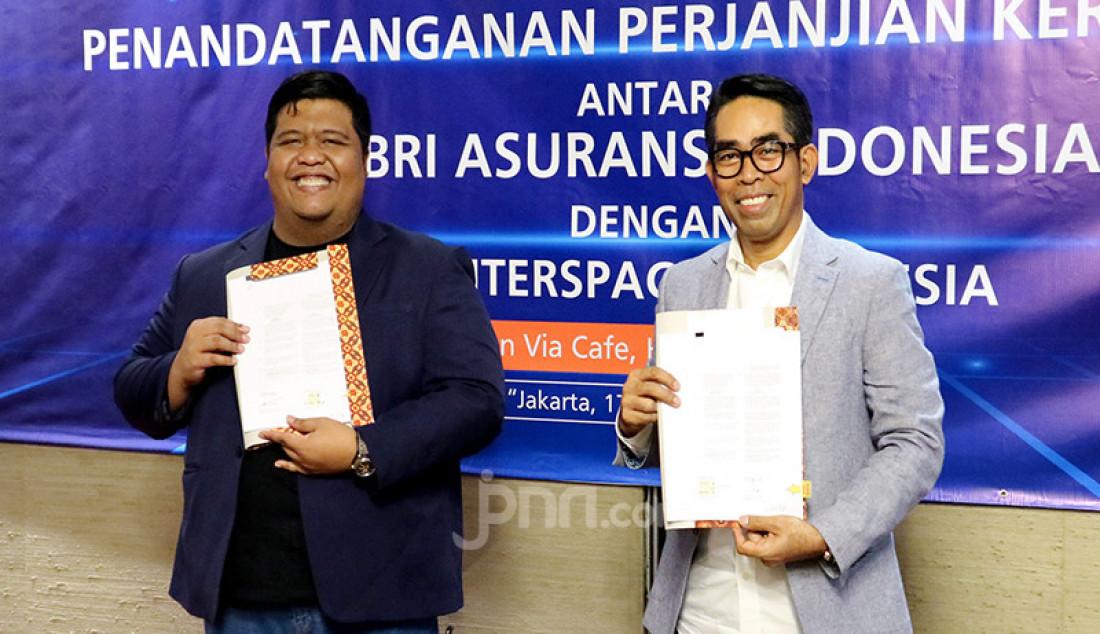 CEO ACCESSTRADE Indonesia Prayudho Rahardjo (kiri) dan Dirut BRI Insurance Fankar Umran saat penandatanganan perjanjian kerja sama Affiliate Marketing antara BRI Insurance (BRINS) dengan ACCESSTRADE Indonesia, Jakarta, Selasa (17/11), guna memperluas jangkauan pasar bisnis asuransi dan produk. Foto: Ricardo - JPNN.com