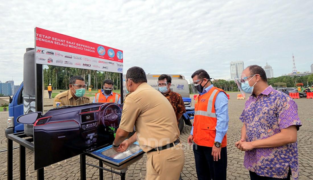 Kepala Unit Pelaksana Teknis (UPT) Monumen Nasional Muhammad Isa Sanuri (kiri) tengah mencuci tangan disaksikan Public Relations & Digital Manager PT Honda Prospect Motor Yulian Karfili (kanan), perwakilan Komunitas Invernity Eric Nainggolan (dua kiri), dan Manajer Peralatan PAM JAYA Mohammad Faizal (dua kanan) saat peresmian fasilitas cuci tangan untuk kawasan Monas di Jakarta Pusat, Selasa (15/12). Komunitas mobil Honda bekerja sama PAM JAYA menyumbangan 45 fasilitas cuci tangan untuk kawasan Monas. Foto: Ricardo - JPNN.com