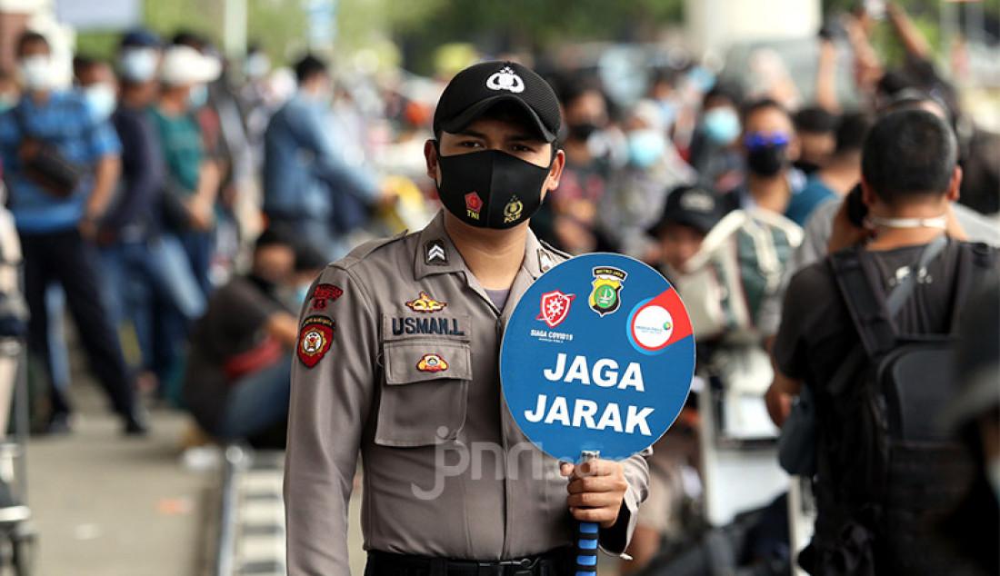 Seorang polisi mengawal jalannya layanan rapid test antigen di Bandara Sokarno Hatta, Tangerang Banten, Selasa (22/12).Para calon penumpang pesawat mengaku harus antre hingga tiga jam untuk mendapatkan layanan rapid tes antigen dengan biaya Rp 200 ribu. Foto: Ricardo - JPNN.com