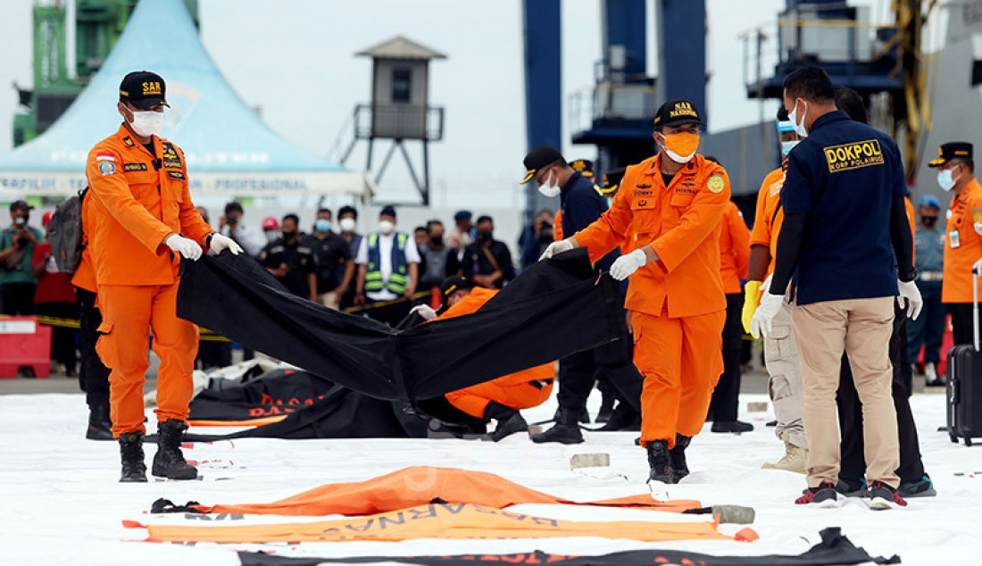 Petugas membawa kantong berisi jenazah dan serpihan dari pesawat Sriwijaya Air SJ182 yang dievakuasi ke Dermaga JICT 2, Jakarta Utara, Minggu (10/1). Foto: Ricardo - JPNN.com