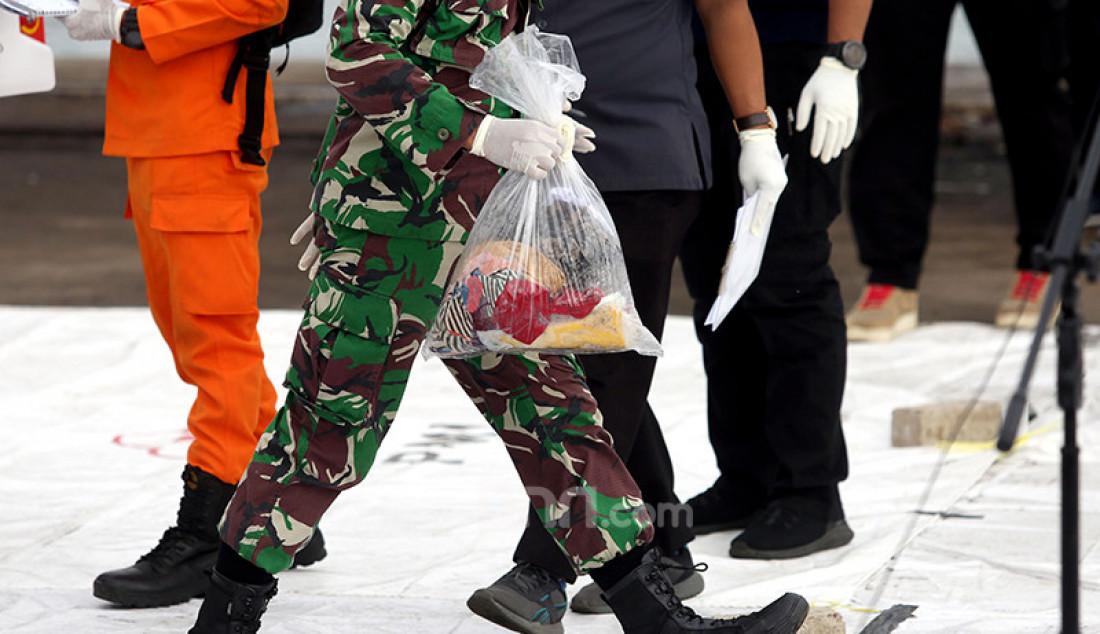Petugas membawa kantong berisi barang milik penumpang pesawat Sriwijaya Air SJ182 yang dikumpulkan di Dermaga JICT 2, Jakarta Utara, Senin (11/1). Foto: Ricardo - JPNN.com