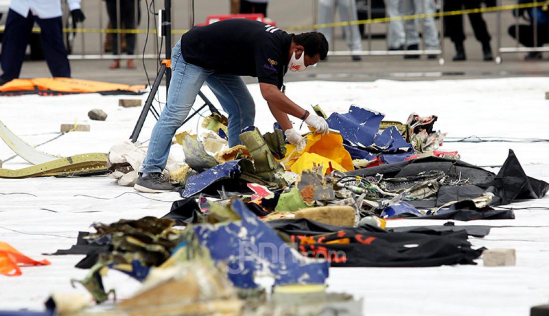 Petugas pencarian dan pertolongan memilah serpihan pesawat Sriwijaya Air SJ 182 yang dikumpulkan di Dermaga JICT 2, Jakarta Utara, Senin (11/1). Foto: Ricardo - JPNN.com
