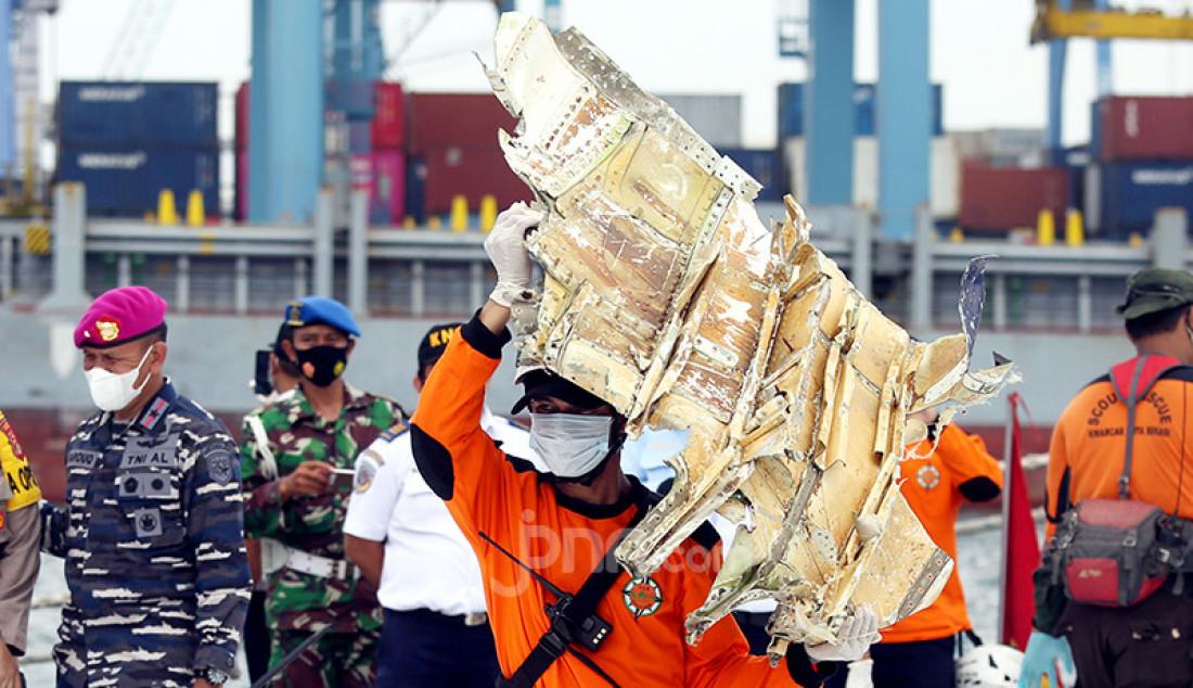 Petugas membawa serpihan pesawat Sriwijaya Air SJ182 di Dermaga JICT 2, Jakarta Utara, Senin (11/1). Foto: Ricardo - JPNN.com