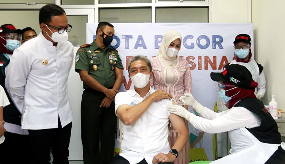 Wakil Wali Kota Bogor Dedie A Rachim (duduk) saat menerima suntikan vaksin Covid-19 di Puskesmas Tanah Sereal, Kota Bogor, Jawa Barat, Kamis (14/1). Wali Kota Bogor Bima Arya Sugiharto turut menyaksikan penyuntikan vaksin Covid-19 kepada wakilnya. Foto: Ricardo - JPNN.com