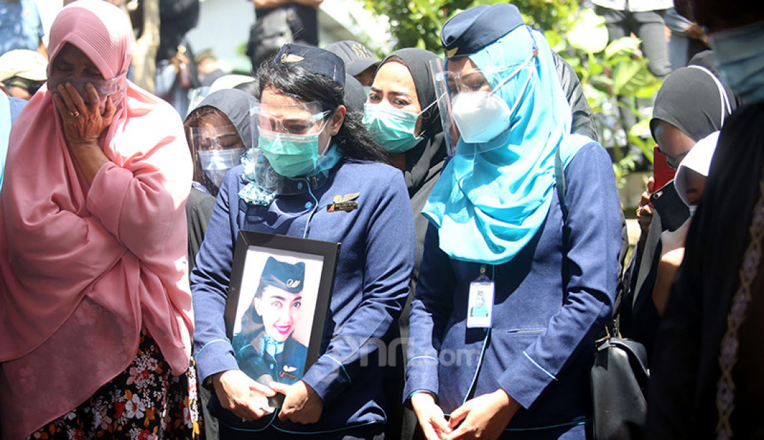 Rekan sesama pramugari menghadiri pemakaman Isti Yudha Prastika di TPU Pondok Petir, Depok, Jawa Barat, Sabtu (16/1). Isti Yudha Prastika merupakan pramugari Nam Air yang menjadi salah satu korban insiden Sriwijaya Air SJ182. Foto: Ricardo - JPNN.com
