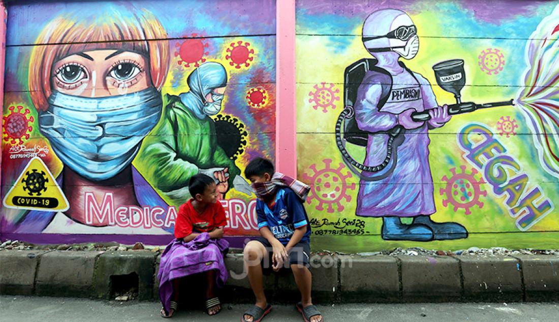Dua bocah tengah duduk di depan mural bertema Covid-19 di kawasan Tanah Tinggi, Tangerang, Banten, Rabu (20/1). Mural tersebut untuk mengingatkan masyarakat akan bahaya Covid-19. Foto: Ricardo - JPNN.com