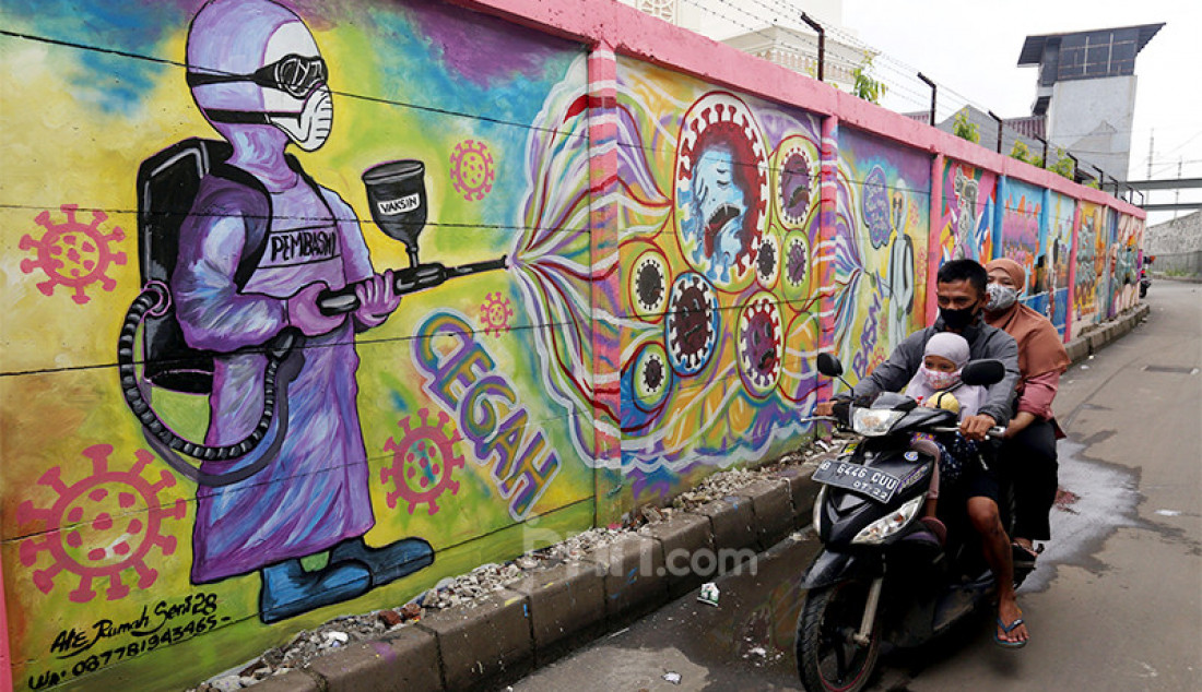 Warga melintas di samping mural bertema Covid-19 di kawasan Tanah Tinggi, Tangerang, Banten, Rabu (20/1). Mural tersebut untuk mengingatkan masyarakat akan bahaya Covid-19. Foto: Ricardo - JPNN.com
