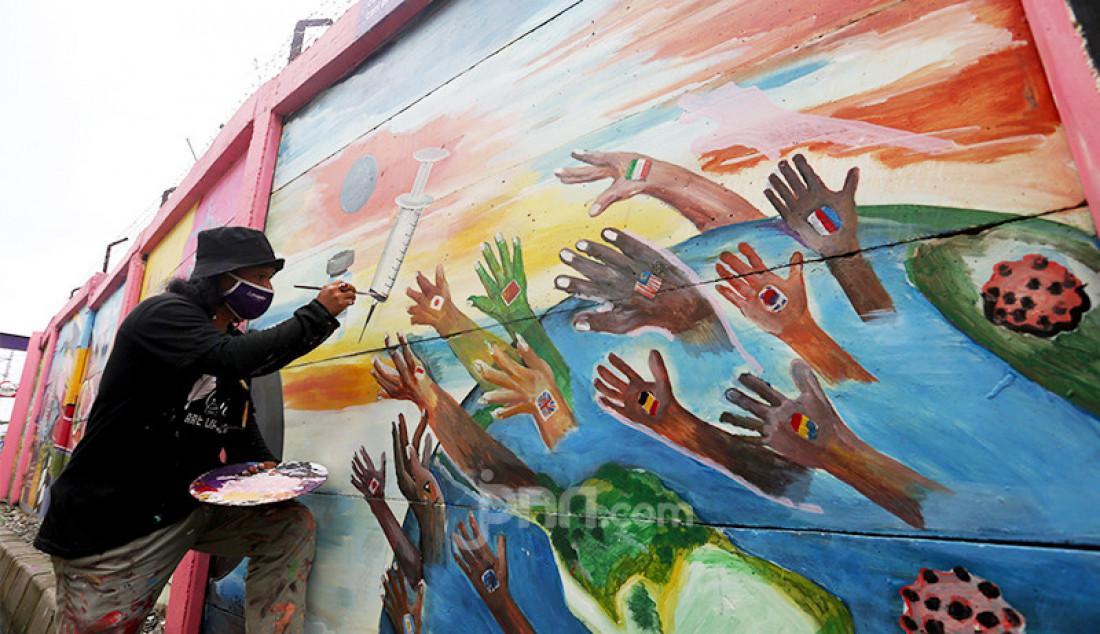 Pekerja seni tengah membuat mural bertema Covid-19 di kawasan Tanah Tinggi, Tangerang, Banten, Rabu (20/1). Mural tersebut untuk mengingatkan masyarakat akan bahaya Covid-19. Foto: Ricardo - JPNN.com