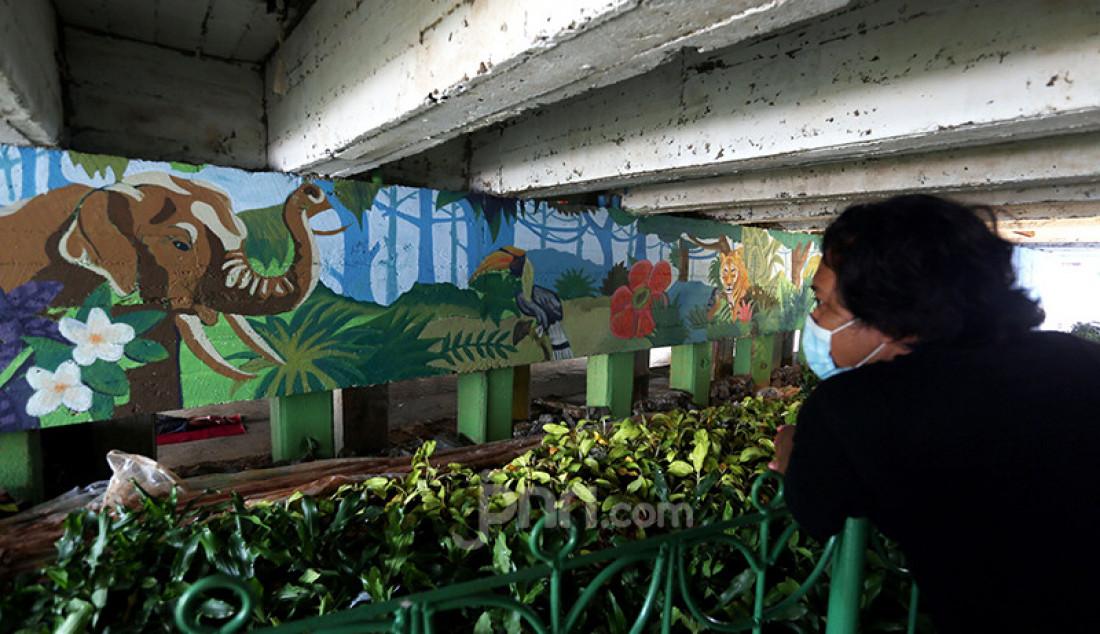 Mahasiswa Institut Kesenian Jakarta (IKJ) menyelesaikan pembuatan mural di kolong Jembatan Pegangsaan, Menteng, Jakarta Pusat, Selasa (26/1). Pembuatan mural tersebut merupakan bagian dari program Pemprov DKI Jakarta tentang pembangunan taman kolong jembatan dalam rangka mempercantik kawasan bantaran kali dan menyediakan ruang interaksi warga. Foto: Ricardo - JPNN.com