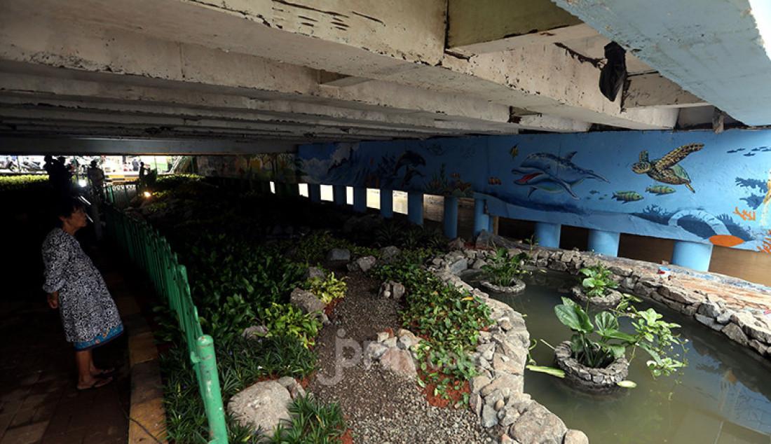 Warga memandangi mural di kolong Jembatan Pegangsaan, Menteng, Jakarta Pusat, Selasa (26/1). Pembuatan mural tersebut merupakan bagian dari program Pemprov DKI Jakarta tentang pembangunan taman kolong jembatan dalam rangka mempercantik kawasan bantaran kali dan menyediakan ruang interaksi warga. Foto: Ricardo - JPNN.com