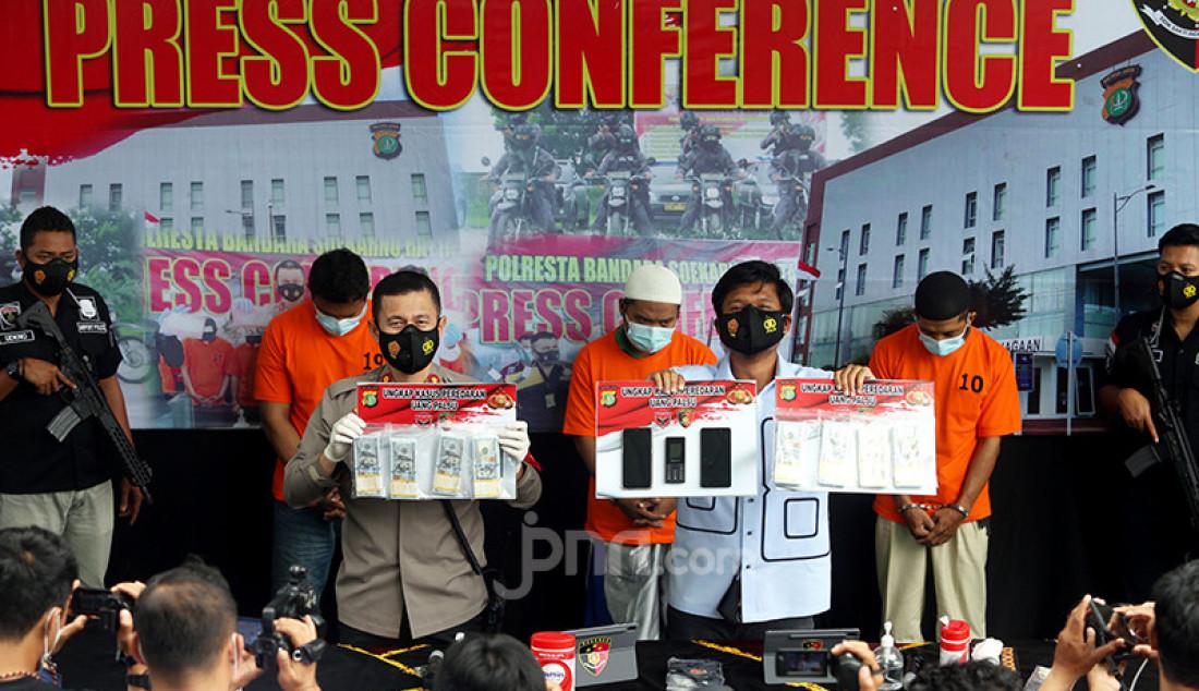 Kapolres Bandara Soetta Kombes Pol Adi Ferdian Saputra (kiri) bersama Kasat Reskrim Polresta Bandara Soetta Kompol Alexander Yurikho saat merilis kasus uang palsu dalam bentuk dolar AS (US) di Taman Integritas Polresta bandara Soekarno Hatta, Tangerang, Banten, Kamis (28/1). Dalam penyidikan kasus itu, polisi telah menetapkan tiga orang sebagai tersangka dan menyita 1.000 lembar USD palsu senilai Rp1,4 miliar. Foto: Ricardo - JPNN.com