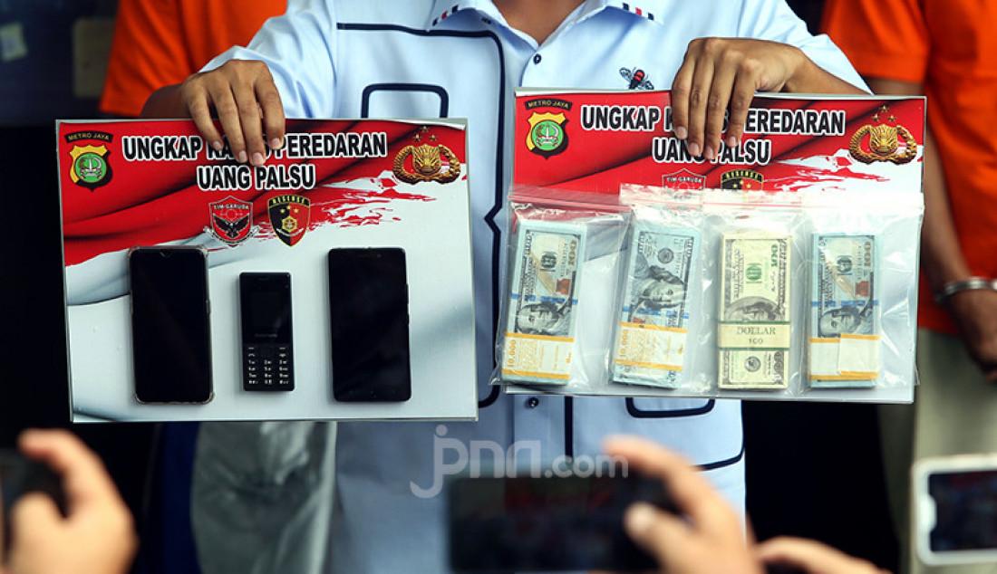 Barang bukti uang dolar palsu beserta alat komunikasi diperlihatkan petugas Polresta Bandara Soetta, Tangerang (28/1) saat rilis bersama tiga orang tersangka. Total sebanyak 1.000 lembar uang palsu senilai Rp 1,4 miliar yang berhasil disita. Foto: Ricardo - JPNN.com