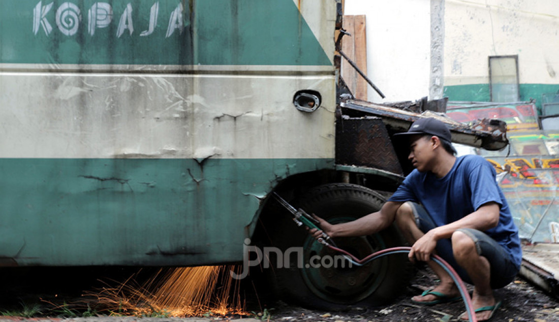 Pekerja membongkar bus Kopaja di kawasan Meruya, Jakarta Barat, Sabtu (30/1). Bus tersebut dijual ke pedagang besi tua lantaran tak dioperasikan lagi seiring program peremajaan Kopaja. Foto: Ricardo - JPNN.com